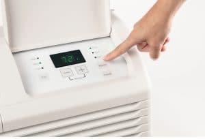 A hand adjusting settings on air conditioning unit from Hotpoint