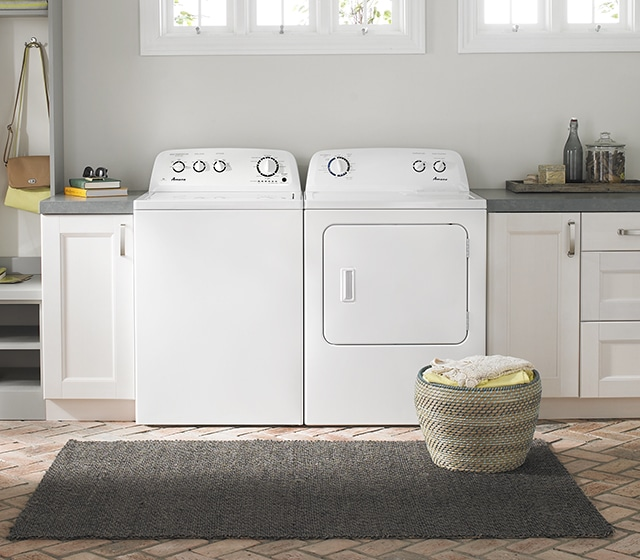 White washer and dryer set with laundry basket in front